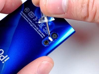 ЭИспользуйте булавку, чтобы удалить маленький белый фиксатор находящийся между камерой и микрофонным отверстием. Это позволит компонентам сползти в сторону нижней части нано.